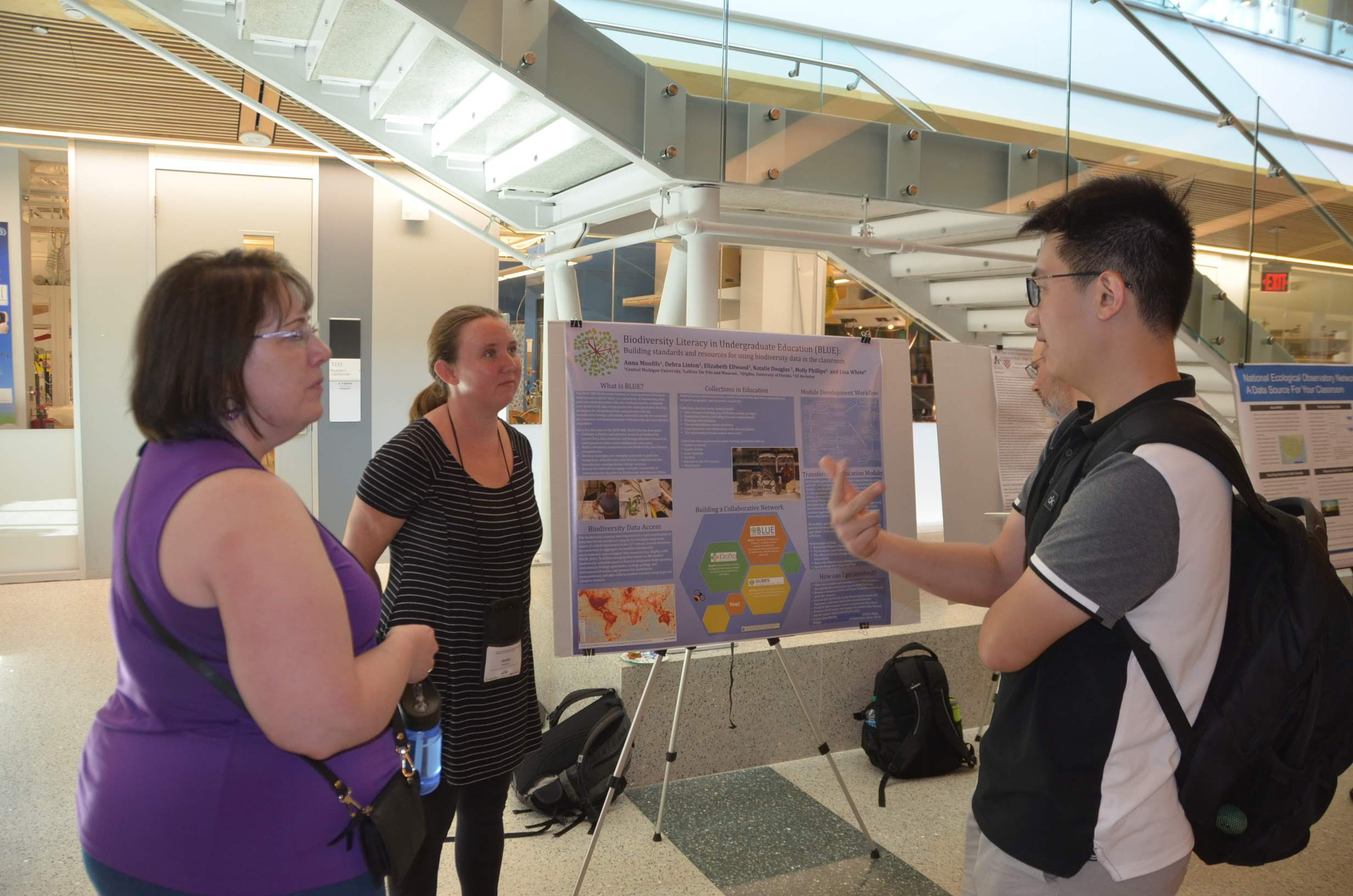Debra Linton and Molly Phillips speaking with a student at the poster session